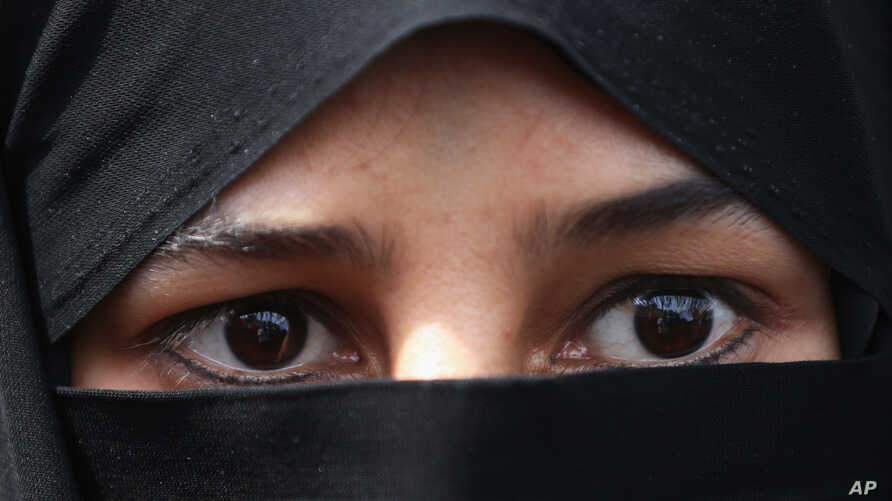 FILE - A veiled Iranian woman attends a rally after the Friday prayers in Tehran, Iran.