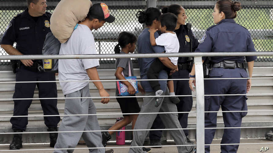 FILE - Ever Castillo (L) and his family, immigrants from Honduras, are escorted back across the border by U.S. Customs and Border Patrol agents, June 21, 2018, in Hildalgo, Texas.