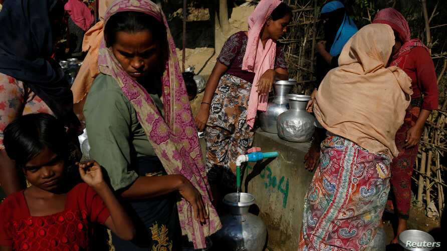 FILE - Rohingya refugee women fill their canisters with water at the Leda refugee camp near Cox's Bazar, Bangladesh, Dec. 16, 2017.