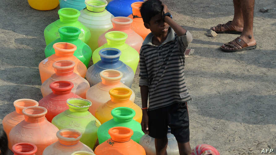 Indian residents queue with plastic containers to get drinking water from a tanker in the outskirts of Chennai, May 29, 2019. An unrelenting heat wave triggered warnings of water shortages and heatstroke in India on June 1.