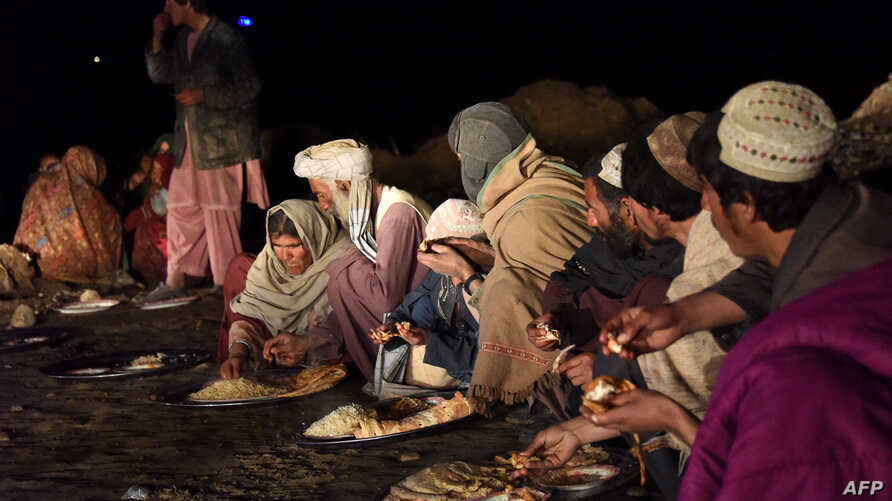 Afghan residents displaced by flooding eat in Arghandab district in Kandahar province, March 3, 2019. Another wave of heavy rain and flooding has claimed at least 24 more in the past month, Afghan officials say.