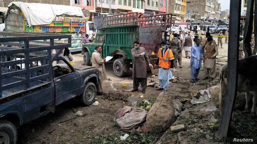 Members of the bomb disposal unit survey the site after a blast at a vegetable market in Quetta, Pakistan, April 12, 2019.
