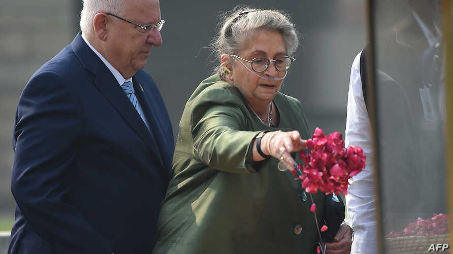 FILE - Israeli President Reuven Rivlin (L) watches as his wife Nechama Rivlin sprinkle rose petals while paying tribute at the Rajghat memorial for Indian independence hero Mahatama Gandhi on his visit to New Delhi, Nov. 15, 2016.