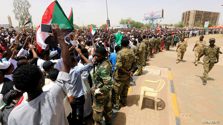 Sudanese military officers control demonstrators as they protest against the army's announcement that deposed president Omar al-Bashir would be replaced by a military-led transitional council, near Defense Ministry in Khartoum, Sudan, April 12, 2019....