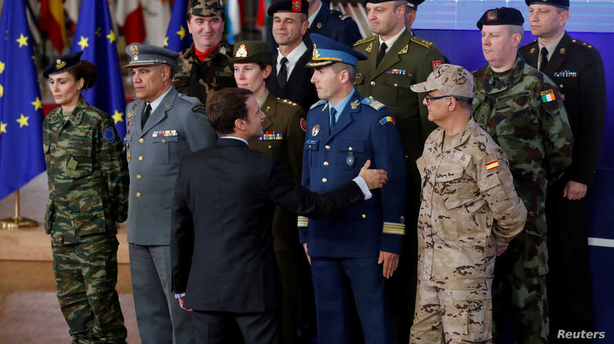 French President Emmanuel Macron greets chief of staff of European countries' armies after the launching of the Permanent Structured Cooperation, or PESCO, a pact between 25 EU governments to fund armed forces,  in Brussels, Belgium Dec. 14, 2017.