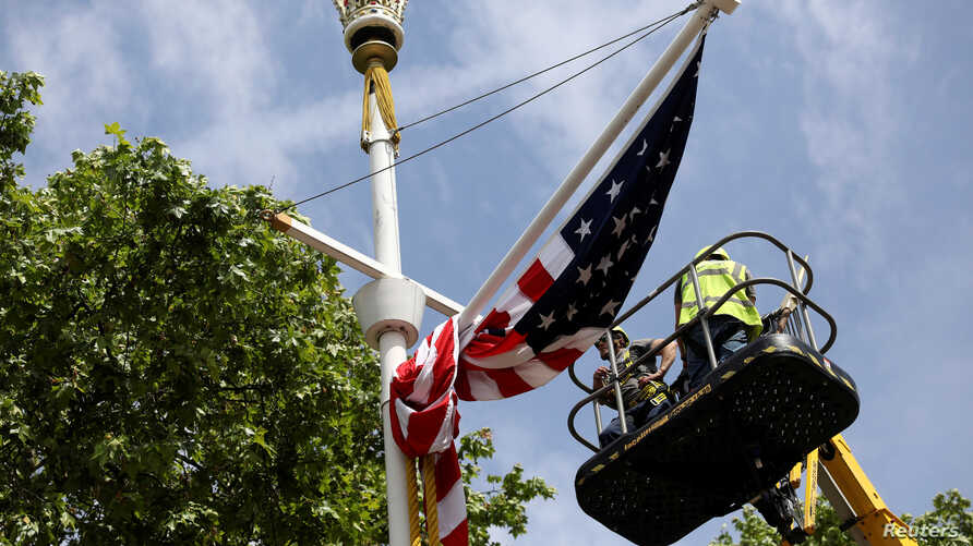 Workers hang a U.S. flag on The Mall towards Buckingham Palace in central London ahead of U.S. President Donald Trump state visit to Britain, June 2, 2019.