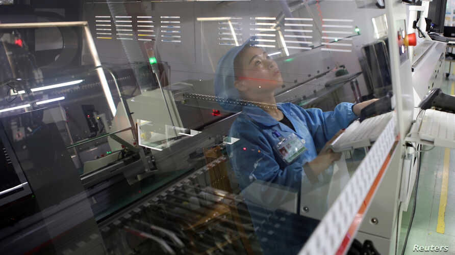 FILE - An employee working on the production line of an electronics factory is seen reflected on an equipment, in Jiaxing, Zhejiang province, China, April 2, 2019.