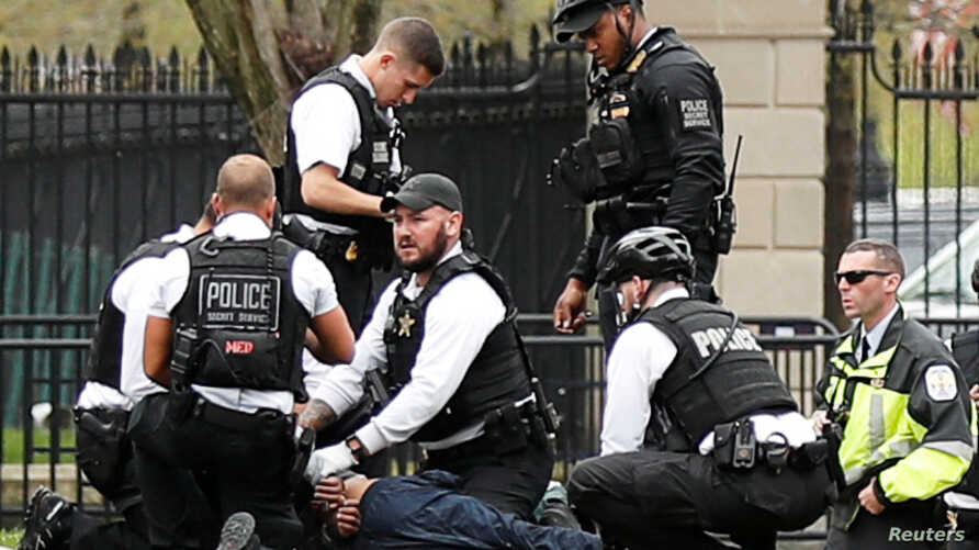 Police and rescue personnel tend to a man in Lafayette Park after the man lit his jacket on fire in front of the White House in Washington, April 12, 2019.