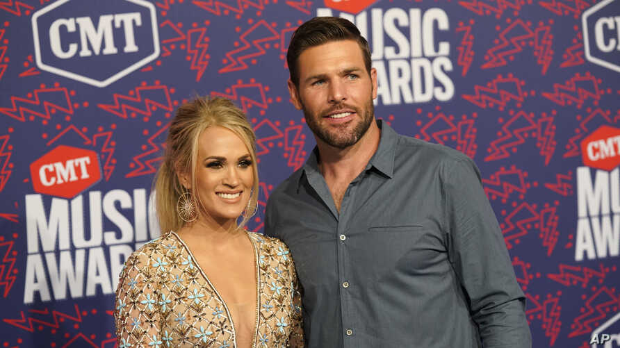 Carrie Underwood, left, and Mike Fisher arrive at the CMT Music Awards on June 5, 2019, at the Bridgestone Arena in Nashville, Tenn.