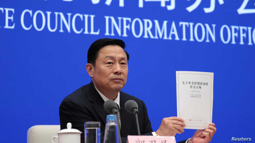"Guo Weimin, Vice Director of the Information Office of China's State Council holds a white paper titled ""China's Position on the China-US Economic and Trade Consultations"" at a news conference in Beijing, June 2, 2019."