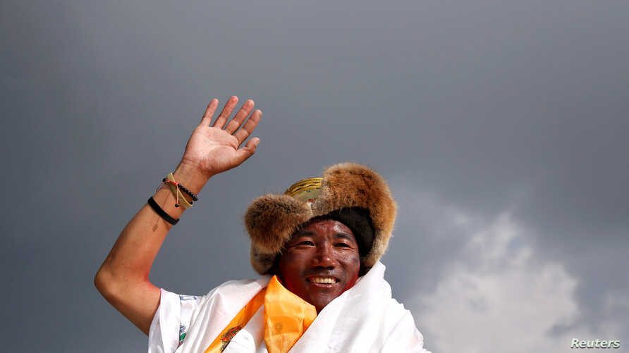 FILE - Kami Rita Sherpa, a Nepali mountaineer, waves toward the media in Kathmandu, Nepal, May 20, 2018.