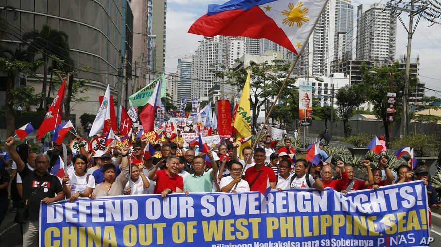 "Hundreds of protesters march for a rally towards the Chinese Consulate to coincide with the country's commemoration of ""Araw Ng Kagitingan"" (Day of Valor) Tuesday, April 9, 2019 in suburban Makati city, east of Manila, Philippines. The protesters are calling on the citizenry to uphold national sovereignty in the wake of China's alleged continued occupation of the disputed islands, shoals and reefs in the South China Sea as well as President Rodrigo Duterte's alleged ""warmer ties with China."" (AP Photo/Bulli"