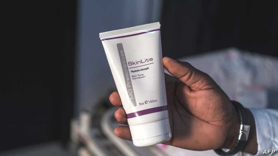 FILE - Aranmolate Ayobami, plastic surgeon at Grandville Medical and Laser clinic in Lagos, holds a tube of Skinlite a skin lightening product used at his clinic, on July 17, 2018, in Lagos, Nigeria.