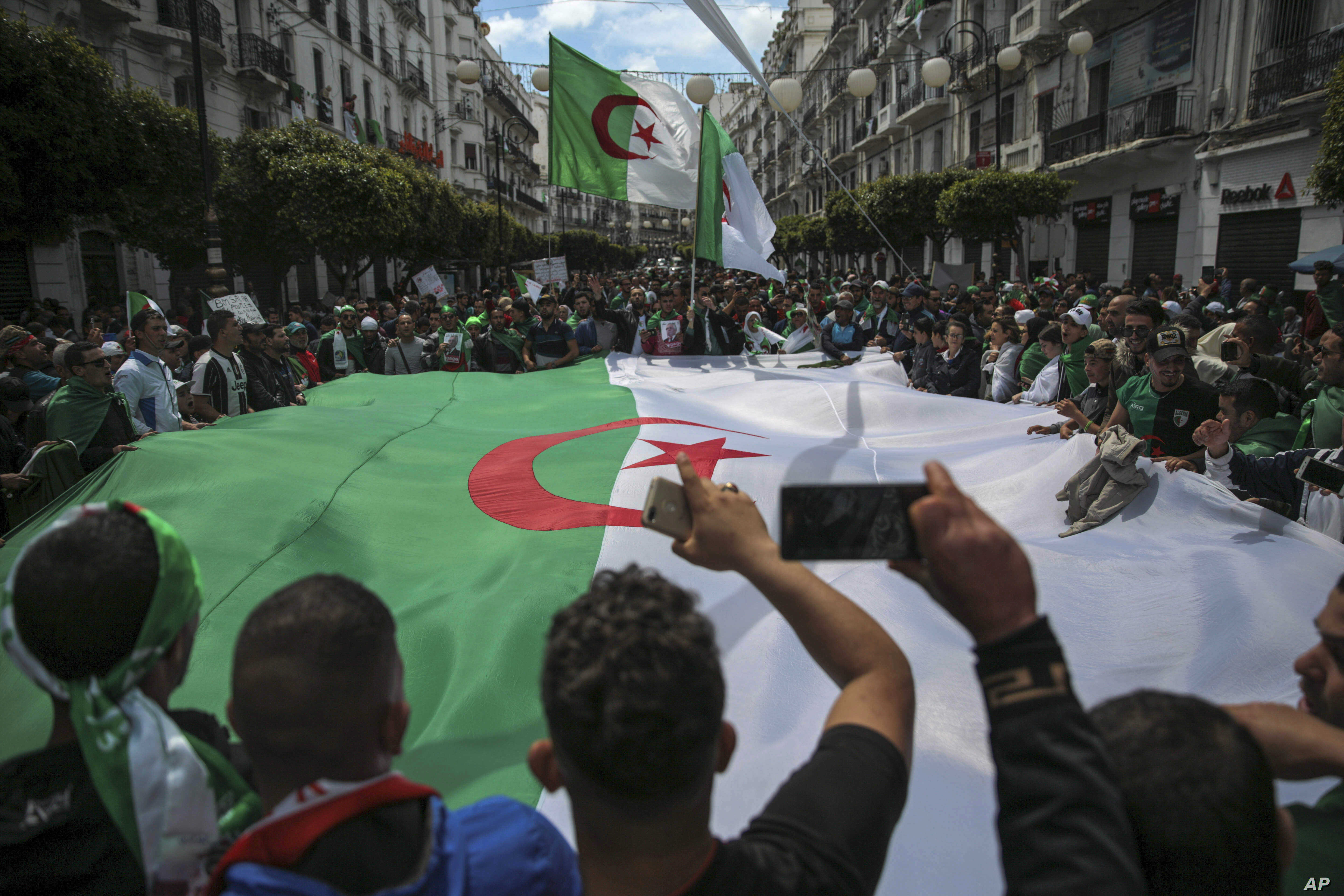 FILE - Protestors carry a large flag and chant slogans during a demonstration against the country's leadership, in Algiers, April 12, 2019.