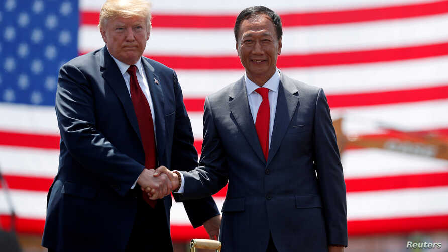 FILE PHOTO:  U.S. President Donald Trump shakes hands with Foxconn Chairman Terry Gou during a grond breaking at Foxconn's new site in Mount Pleasant, Wisconsin, June 28, 2018.