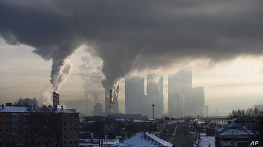 FILE - Smoke rises from a Moscow power station with Moscow's City Center skyscrapers visible in the background in Moscow, Russia.