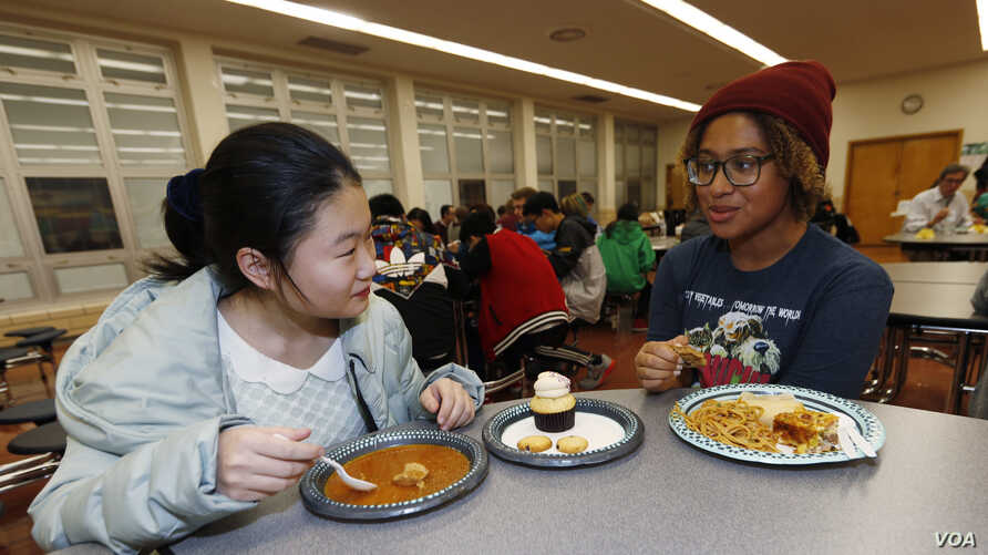 In this Jan. 27, 2017 photo, foreign exchange student Miaofan Chen, left, of Hefei, China, chats with Thandi Glick in Denver.
