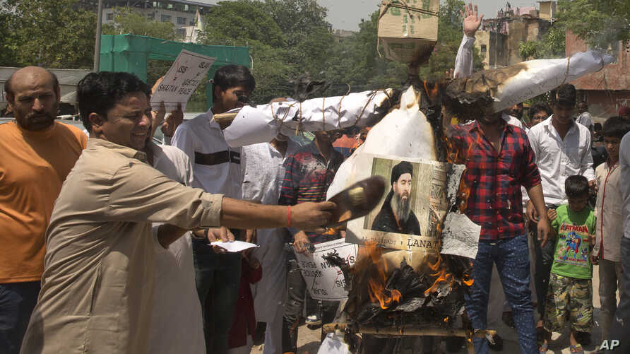 FILE - Shiite Muslims shout slogans and burn an effigy of the leader of the Islamic State group, Abu Bakr al-Baghdadi during a protest in New Delhi, India, Friday, June 9, 2017.