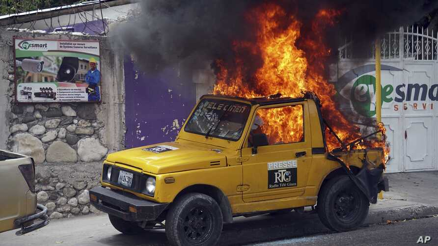 Fire blazes inside jeep belonging to Radio-Tele Guinen in Port-au-Prince, Haiti