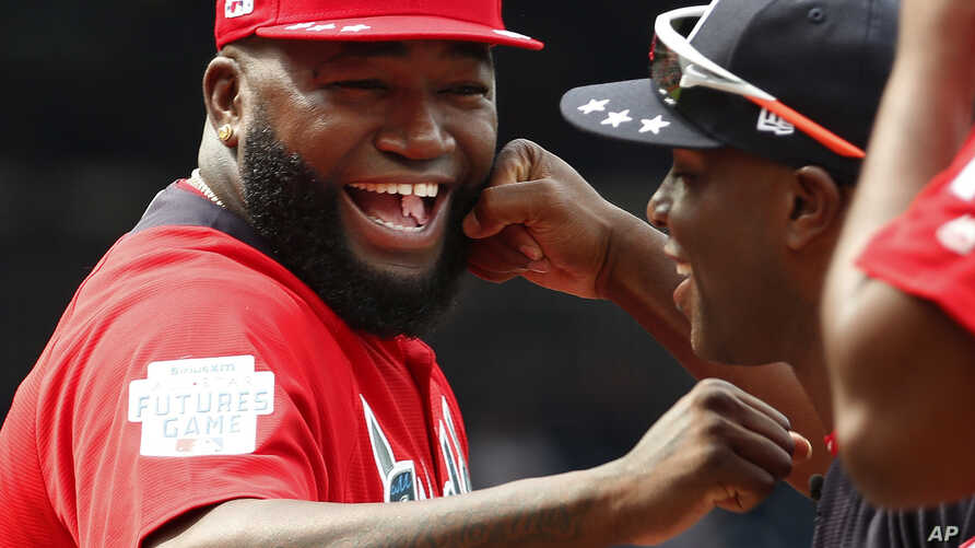 FILE - World Team Manager David Ortiz (34) speaks with U.S. Team Manager Torrii Hunter, before the All-Star Futures baseball game at Nationals Park, in Washington, July 15, 2018.