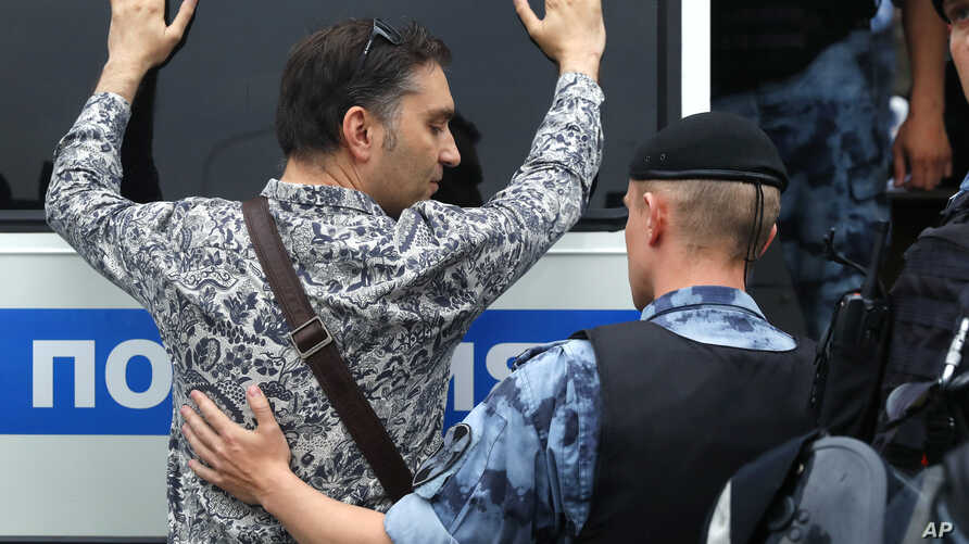 Police officer detains a supporter of Russian investigative journalist Ivan Golunov during a march in Moscow, Russia, Wednesday, June 12, 2019.