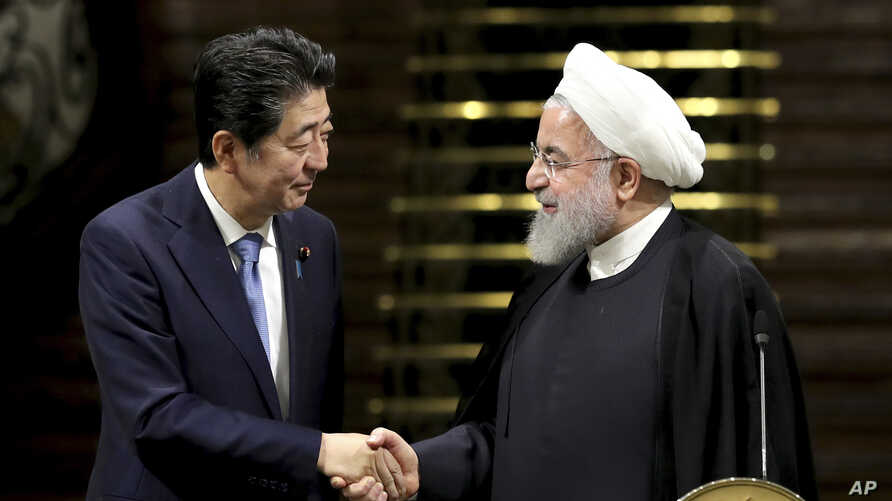 Japanese Prime Minister Shinzo Abe, left, and Iranian President Hassan Rouhani shake hands after their joint press conference at the Saadabad Palace in Tehran, Iran, June 12, 2019.