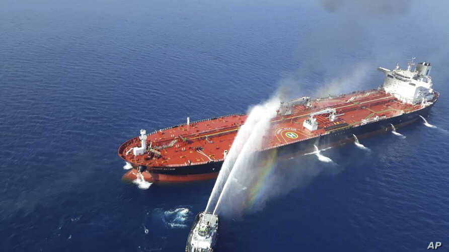 An Iranian navy boat sprays water to extinguish a fire on an oil tanker in the Gulf of Oman,  June 13, 2019.