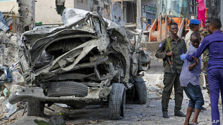Security forces stand near the wreckage of an official vehicle that was destroyed in a bomb attack in the capital Mogadishu, Somalia Saturday, June 15, 2019.
