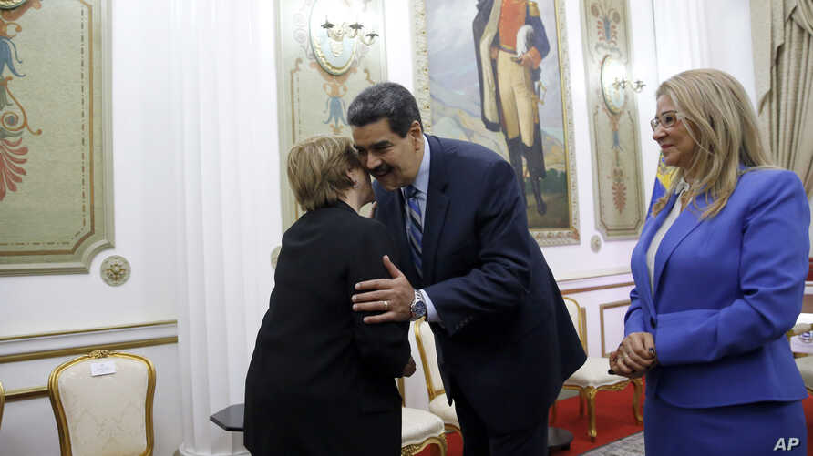U.N. High Commissioner for Human Rights Michelle Bachelet, left, is greeted by Venezuela's President Nicolas Maduro, as first lady Cilia Flores looks on, at Miraflores Presidential Palace, in Caracas, Venezuela, Friday, June 21, 2019.