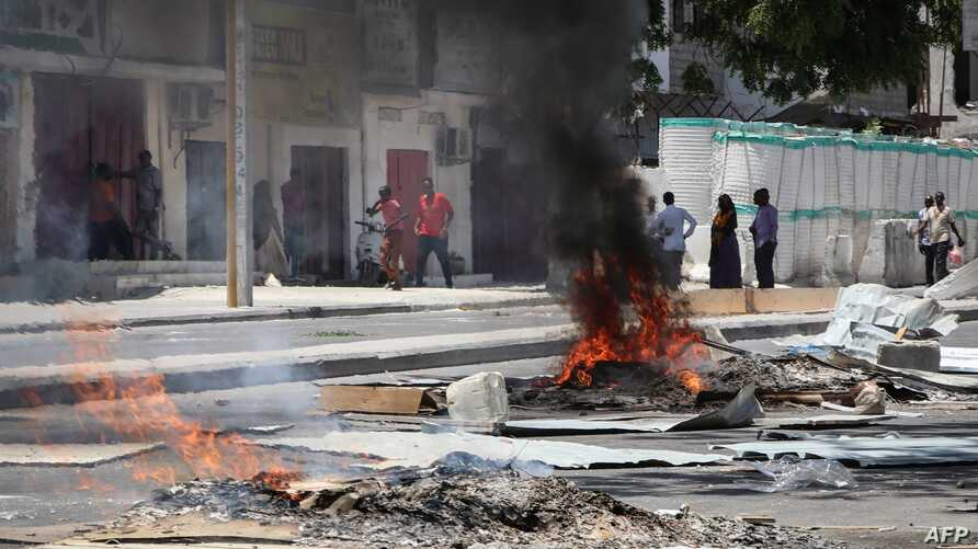 Fires are seen on a street following protests against the shooting of a rickshaw driver and his passenger, April 13, 2019, in Mogadishu.