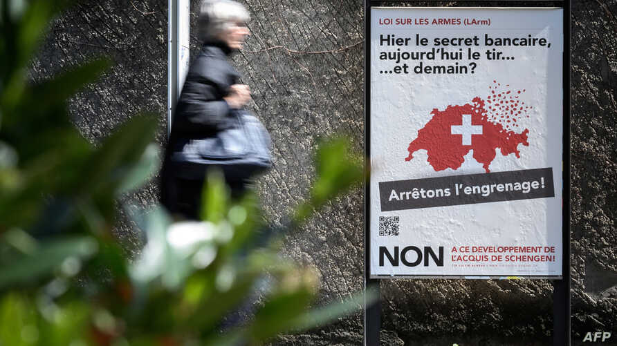 "A woman walks past a campaign poster against toughening gun laws in Switzerland. It reads in French, ""Yesterday banking secrecy, today shooting ... and tomorrow? Let's stop the spiral!"" May 13, 2019, in Geneva."