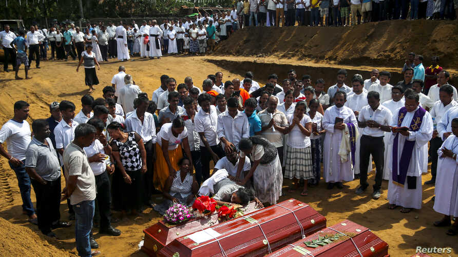 People react during a mass burial of victims, two days after a string of suicide bomb attacks on churches and luxury hotels across the island on Easter Sunday, at a cemetery near St. Sebastian Church in Negombo, Sri Lanka, April 23, 2019.
