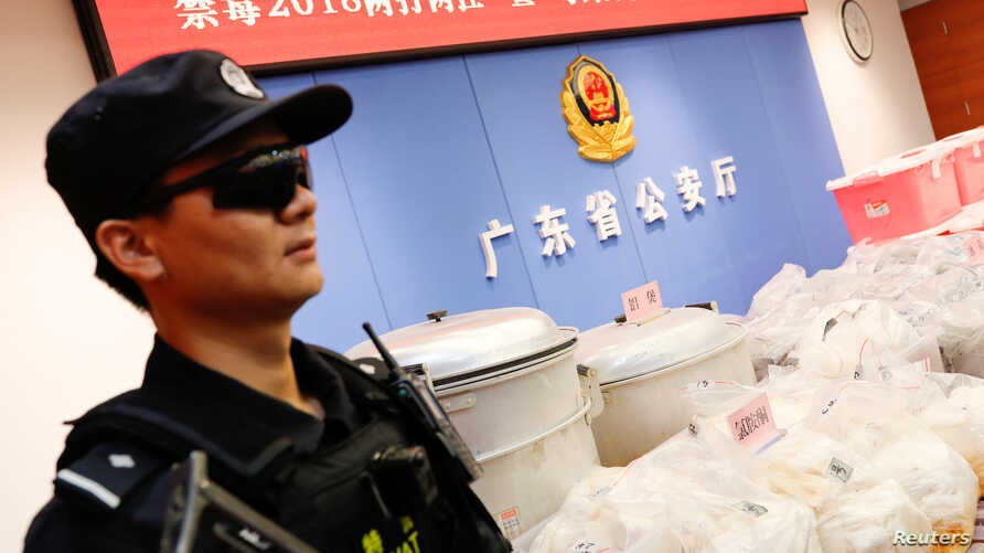 FILE L- A police officer stands guard next to seized drugs in Shenzhen, Guangdong province, China, April 24, 2018.