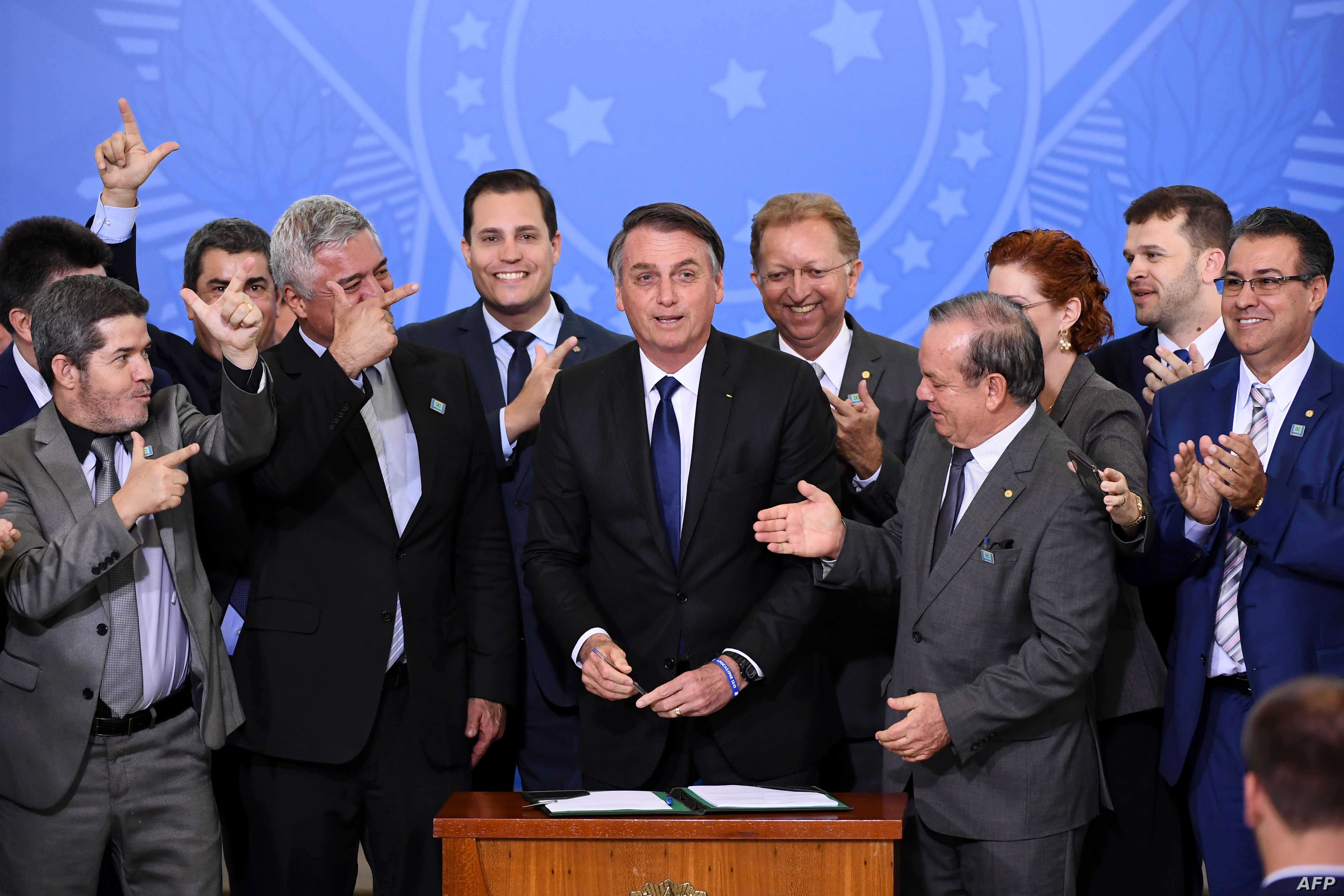 FILE - Brazilian President Jair Bolsonaro, center, is pictured surrounded by parliamentarians during the signing ceremony of the decree that facilitates to own, carry and import weapons, at the Planalto Palace in Brasilia, May 7, 2019.