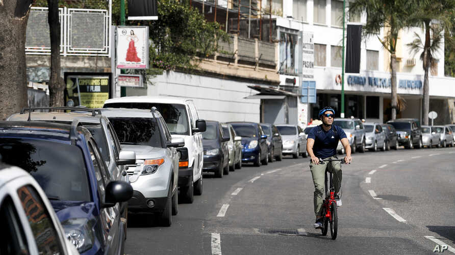 FILE - A cyclist pedals through an empty street, past motorists waiting to fill up at one of the few fuel stations that has electricity, during rolling blackouts in Caracas, Venezuela, March 10, 2019. On Friday, Venezuelans waited hours in line for g...