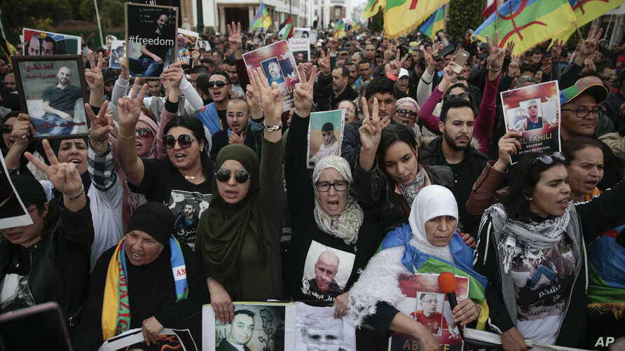Thousands of Moroccans wave Berber flags and hold photos of detained activists as they take part in a demonstration in Rabat, Morocco, Sunday, April 21, 2019. Protesters are condemning prison terms for the leader of the Hirak Rif protest movement aga...
