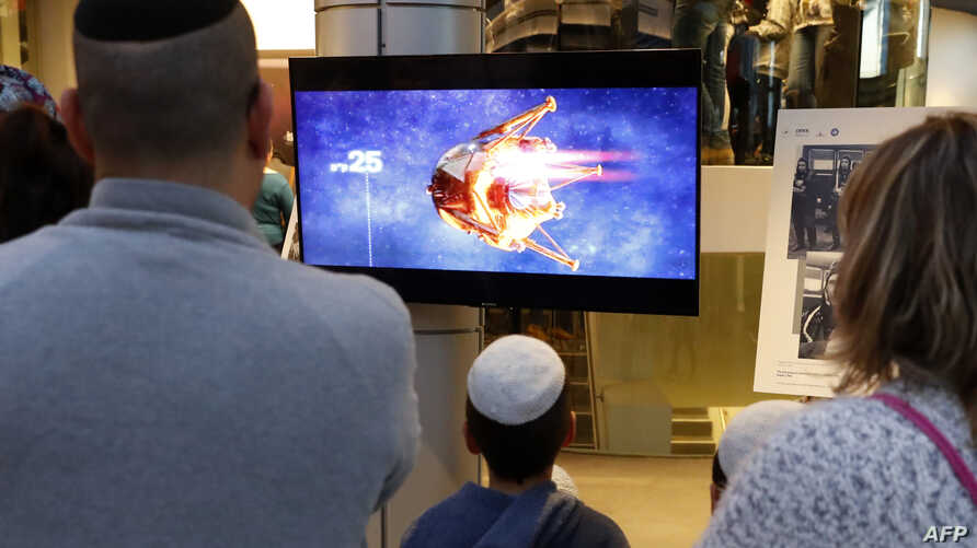 People watch a screen showing explanations of the planned landing of Israeli spacecraft Beresheet at the Planetaya Planetarium in the Israeli city of Netanya, April 11, 2019, before it crashed during the landing.
