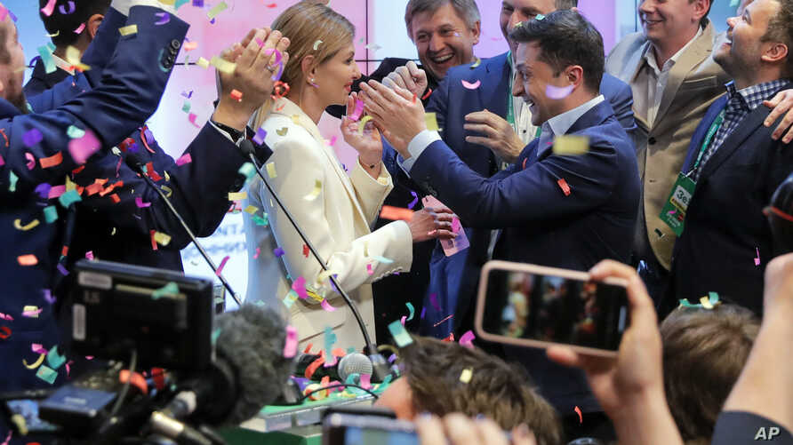Ukrainian comedian and presidential candidate Volodymyr Zelenskiy, center right, and his wife Olena Zelenska, center left, greet their supporters at his headquarters as the portrait of Ukrainian President Petro Poroshenko is seen on a TV screen, righ...