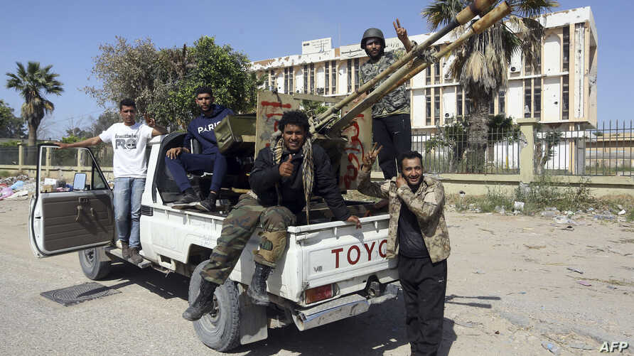 Forces loyal to Libya's Government of National Accord gesture, April 18, 2019, after taking control of the area of al-Aziziyah, located about 40 kilometers south of the Libyan capital Tripoli, following fierce clashes with forces loyal to strongman K...
