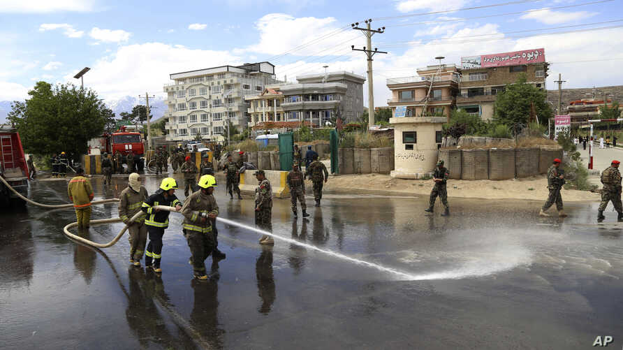 Afghan firefighters clean the site of a suicide bombing targeting a military academy in Kabul, Afghanistan, May 30, 2019. The suicide bomb killed at least six people and wounded six others Thursday, the Interior Ministry said.