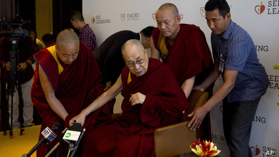 Tibetan spiritual leader, the Dalai Lama, center, is assisted by his aides as he arrives to interact with an audience of educators, in New Delhi, India, April 4, 2019.