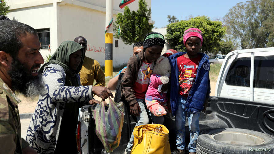Members of Libyan internationally-recognized government forces evacuate an African family during the fighting with Eastern forces, at Al-Swani area in Tripoli, Libya, April 18, 2019.