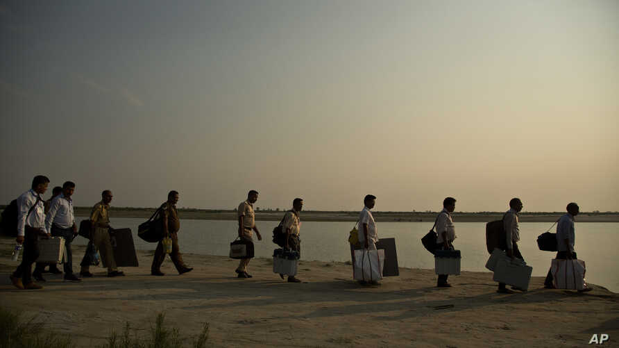 Indian election officials with polling materials walk to board a country boat to reach a polling center in a remote river island in the River Brahmaputra in Kamrup district, west of Gauhati, Assam, India, April 22, 2019.