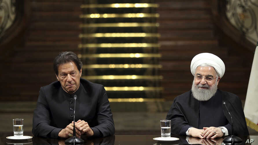 In this photo released by the official website of the office of the Iranian Presidency, President Hassan Rouhani, right, and Pakistani Prime Minister Imran Khan, attend a joint press briefing, after their meeting at the Saadabad Palace in Tehran, Ira...
