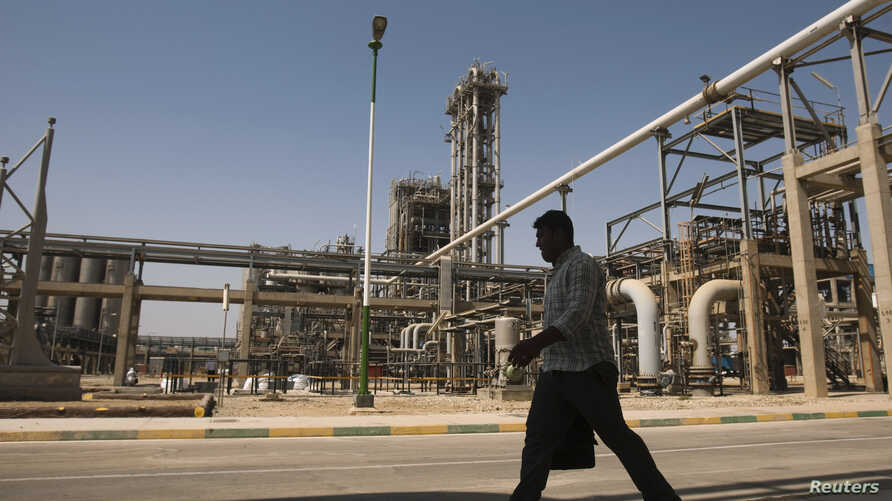 FILE - A man walks past the Mahshahr petrochemical plant in Khuzestan province,1032 km (641 miles) southwest of Tehran, Sept. 28, 2011.