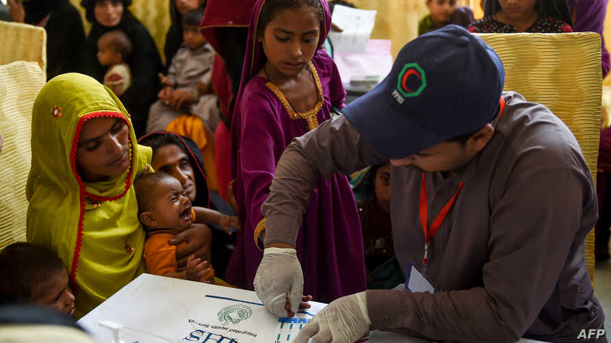 In this image taken on May 9, 2019, a Pakistani paramedic takes a blood sample from a girl for a HIV test at a state-run hospital in Rato Dero in the district of Larkana of the southern Sindh province.
