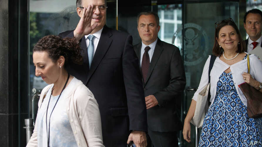 Marcelo Ebrard, Mexico's Secretary of Foreign Affairs, second from left, waves as he and members of his staff walk out of the State Department after a meeting to talk about tariffs, June 6, 2019, in Washington. (AP Photo/Jacquelyn Martin)