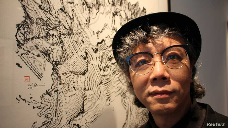 Hong Kong artist Victor Wong stands next to an artwork from his exhibition 'Far Side of the Moon' at 3812 Gallery in London, Britain, April 16, 2019.