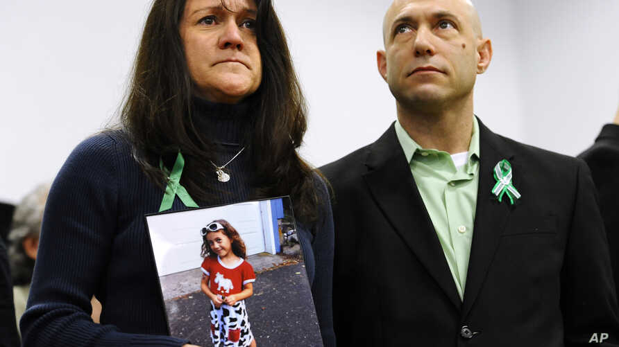 Jeremy Richman, with wife Jennifer Hensel holding a portrait of their daughter, Avielle Rose Richman, who was killed in the Sandy Hook school shooting, Newtown, Conn., Jan. 14, 2013.