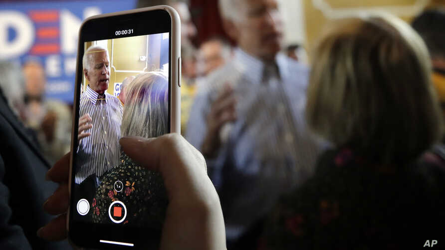An attendee records former vice president and Democratic presidential candidate Joe Biden during a campaign event, June 4, 2019, in Berlin, New Hampshire.